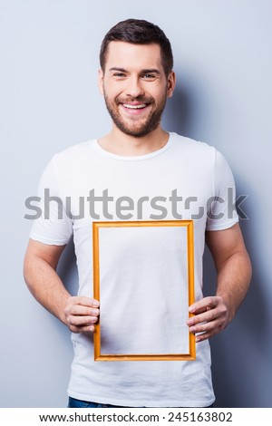 Copy space in frame. Handsome young man in T-shirt holding a picture frame while standing against grey background  - stock photo