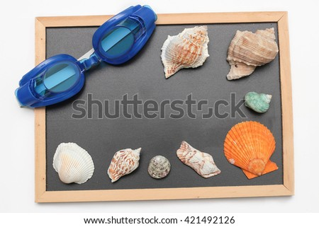Copy space on chalk board with swimming goggle and shell - vacation and business concept - stock photo