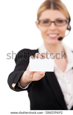 Copy space on her card. Confident mature customer service representative in headset stretching out hand with business card and smiling while standing isolated on white - stock photo