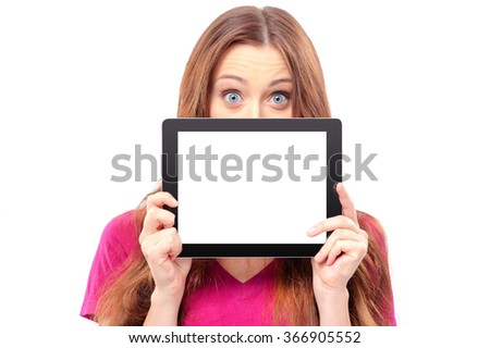 Copy space on her digital tablet. Surprised young woman looking out of the digital tablet while standing isolated on white - stock photo