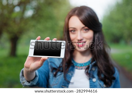 Copy space on her smartphone. Attractive young caucasian woman showing her mobile phone screen and smiling. Outdoors portrait. - stock photo