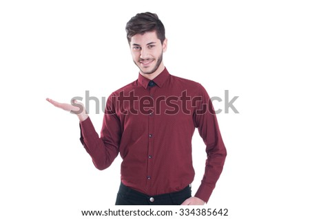 Copy space on his hand. Handsome young man in shirt looking at camera and holding copy space while standing against white background - stock photo