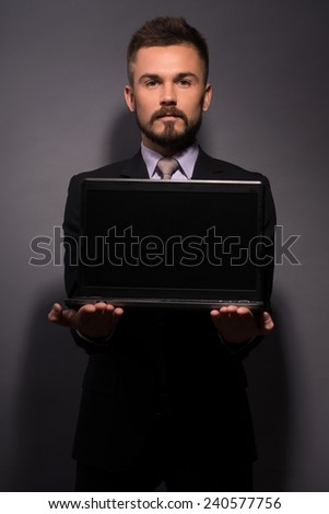 Copy space on his laptop. Image of handsome businessman in formalwear showing a screen of his laptop while standing against grey background - stock photo