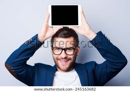 Copy space on his tablet. Cheerful young man holding a digital tablet upon his head and smiling while standing against grey background - stock photo