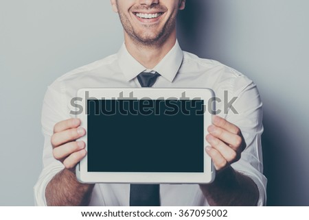 Copy space on his tablet. Cropped  image of cheerful young man showing his digital tablet and smiling while standing against grey background - stock photo
