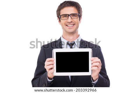 Copy space on his tablet. Handsome young man in formalwear and glasses showing monitor of his digital tablet and smiling while standing isolated on white background - stock photo