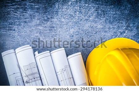 Copy space version of white rolled blueprints and construction helmet on metallic scratched background building and architecture concept. - stock photo