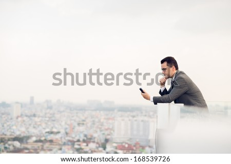Copy-spaced image of a businessman making a telephone call while standing on the roof  - stock photo