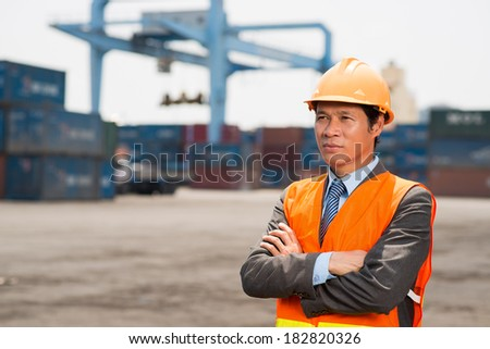 Copy-spaced image of a confident worker controlling seaport  - stock photo