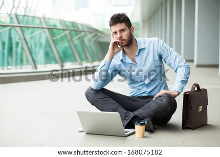Copy-spaced image of a contemplating businessman sitting in front of the laptop on the floor