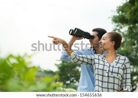 Copy-spaced image of a couple where a man with binoculars and his woman pointing at something - stock photo