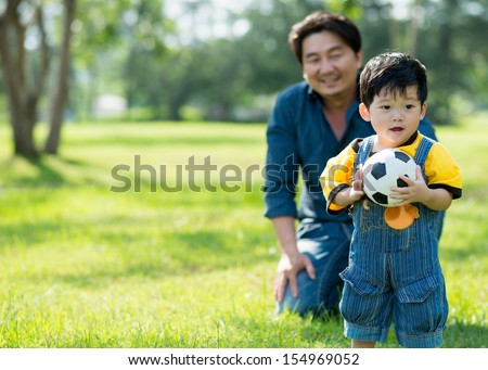 Copy-spaced image of a cute baby boy with a ball in hands - stock photo