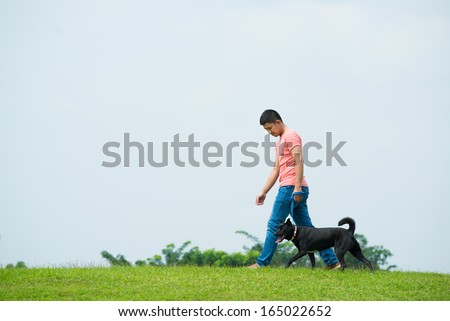 Copy-spaced image of a dog-owner walking with his pet on the green lawn  - stock photo