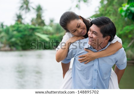 Copy-spaced image of a fun husband giving his wife a piggyback - stock photo