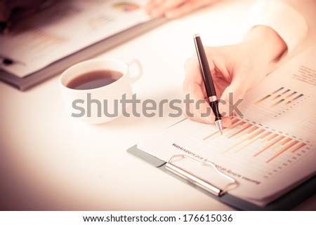 Copy-spaced image of a male hand holding a ballpoint and analyzing the financial growth of the company  - stock photo