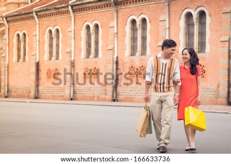 Copy-spaced image of a senior couple having promenade after shopping  - stock photo