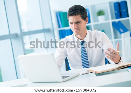 Copy-spaced image of a serious businessman at work at the office on the foreground