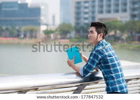 Copy-spaced image of a young fashionable guy with a book on the foreground  - stock photo