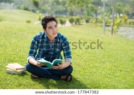 Copy-spaced image of a young guy reading a book in the park  - stock photo