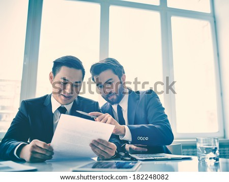 Copy-spaced image of business colleagues analyzing the document at the office  - stock photo