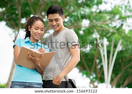 Copy-spaced image of students where a teenage girl explaining the homework to his fellow-student outside - stock photo
