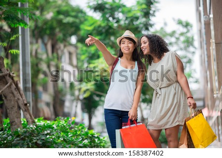 Copy-spaced image of young shopaholics pointing at the mall standing outside - stock photo