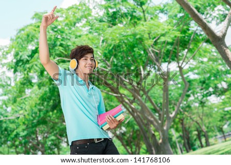 Copy-spaced of a cool guy listening to the music in the park - stock photo