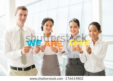 Copy-spaced portrait of a business international team holding colorful letters and looking at camera  - stock photo