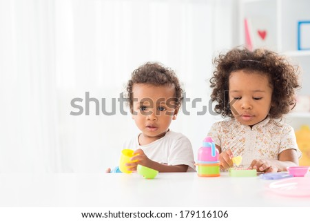 Copy-spaced portrait of a little boy looking at camera while his sister playing on the foreground  - stock photo