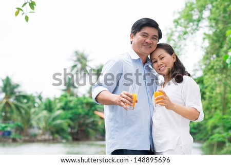 Copy-spaced portrait of a mature couple in-love standing and posing at camera outside - stock photo
