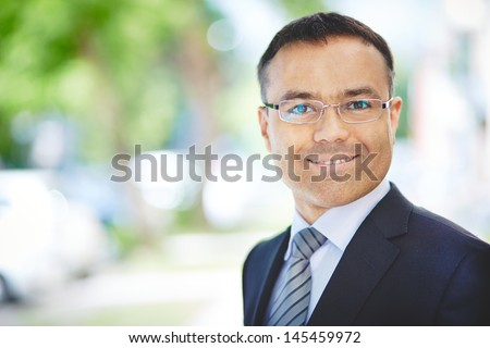 Copy-spaced portrait of a positive white-collar worker looking at the camera - stock photo