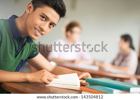 Copy-spaced portrait of a student sitting with books and looking at camera - stock photo