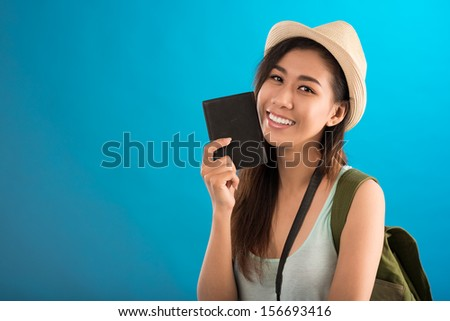 Copy-spaced portrait of a young female traveler with an international passport in hand smiling and looking at camera over a blue background - stock photo