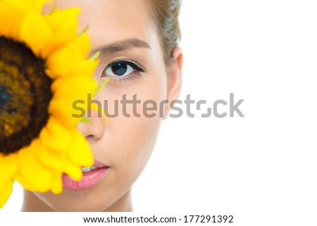 Copy-spaced portrait of a young woman with a sunflower looking at camera on the foreground  - stock photo