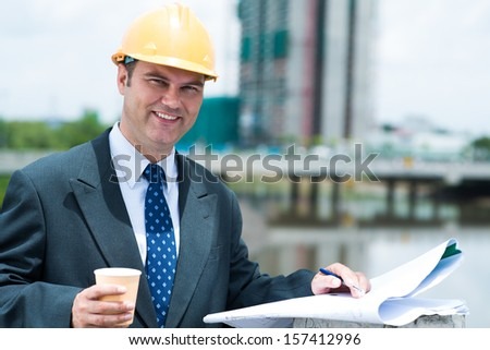 Copy-spaced portrait of an engineer having coffee break outside - stock photo