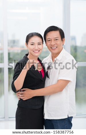 Copy-spaced portrait of happy owners of new apartments showing the keys  - stock photo