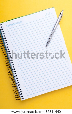 copybook and pen on a yellow background