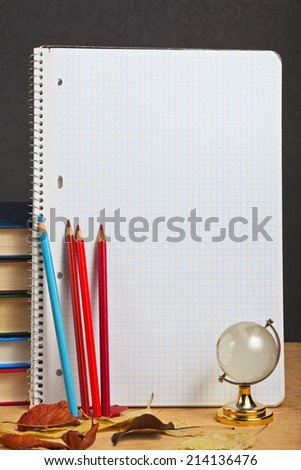 Copybook with colored pencils and autumn leaves. - stock photo