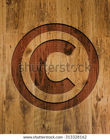 Copyright symbol engraved in wooden background. - stock photo