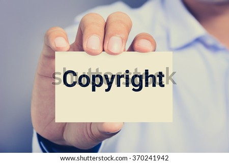 Copyright word on the card shown by a man - stock photo