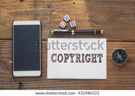 Copyright Word written on white on wooden desk with dice,compass,smart phone and pen.Top view conceptual - stock photo