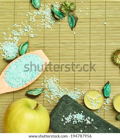 Copyspace bamboo mat background covered with aromatic salt, candles, towel and apple