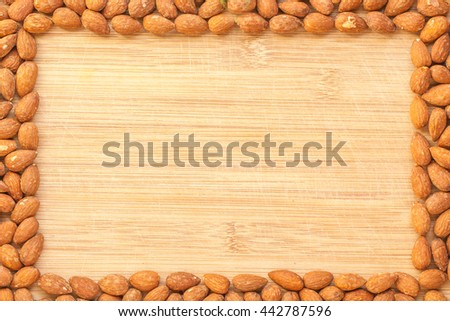 Copyspace composition with the borders made of almond seeds over the wooden cutting board background. Rectangular border or frame of fresh raw almonds rich in vitamin e, protein and dietary fiber. - stock photo