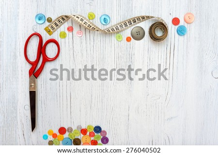 Copyspace frame with sewing tools and accesories on white wooden background - stock photo