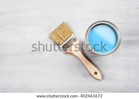 Copyspace with paintbrush and can with blue paint lying on white wooden clean table. Top view. Copyspace. - stock photo