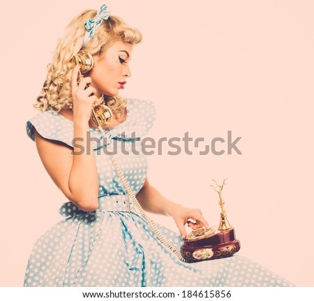 Coquette blond pin up style young woman in blue dress with vintage phone  - stock photo