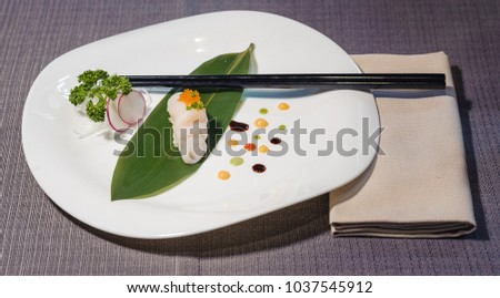 Coquilles Saint Jacques with caviar nigiri on a bamboo leaf served with daikon and radish julienne, traditional Japanese food, fresh fish on a rice patty