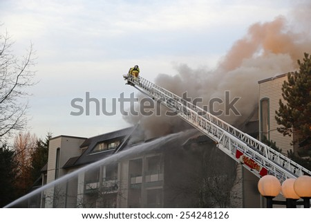 Coquitlam, BC, Canada - February 16, 2015 : Firefighter crews battling apartment complex fire on Glen drive in Coquitlam. - stock photo