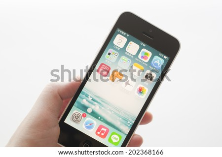 Coquitlam BC Canada - July 02, 2014 : Apple iPhone in a female hand, the iPhone is one of the most popular smart phones in the world and produced by Apple Computer, Inc.  - stock photo