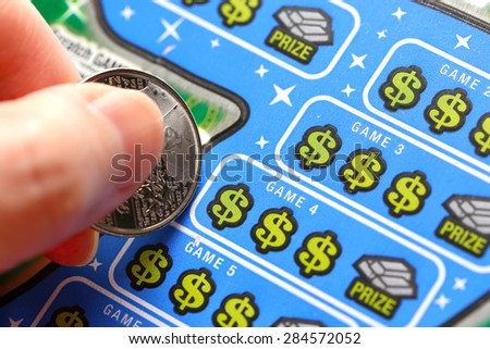 Coquitlam BC Canada - June 02, 2015 : Woman scratching lottery tickets. The British Columbia Lottery Corporation has provided government sanctioned lottery games in British Columbia since 1985.  - stock photo